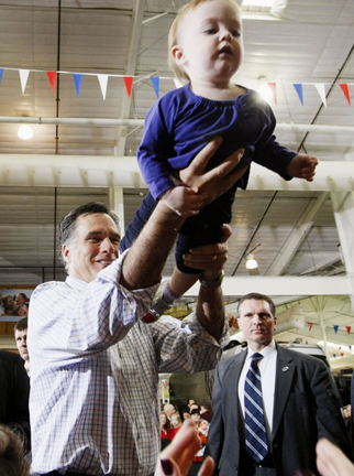 Republican presidential candidate Mitt Romney hands Madison Busch, 1, to her mother after a campaign event at an RV dealer in Loveland