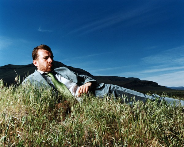 """Businessman lying on grass, Steens Mountains, Oregon, USA,"" by Matthias Clamer"