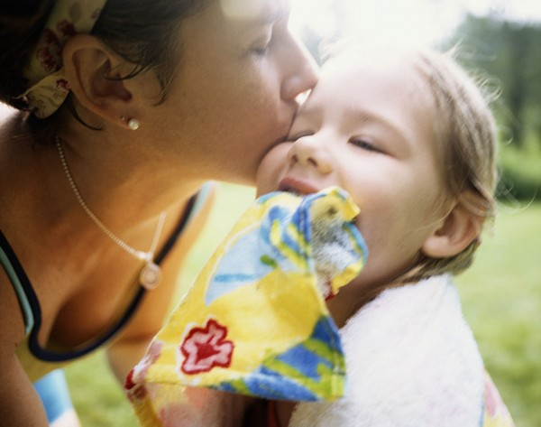"""Mother kissing daughter (4-6), close-up,"" by Jim Bastardo"