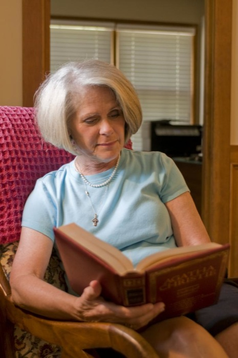 This woman pictured here from an anterior view, was reading a novel by the authoress, Agatha Christie, in the comfort of her home. The book's pages were well-lit, thereby, reducing the possibility of eye-strain.