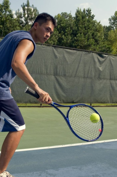 Caught in a mid-backhand swing, this young man was playing a game of tennis on the court. Wearing a darkly-colored tank top, loose-fitting shorts, and a protective layer of sunscreen, all helped block ultraviolet rays from damaging his sun-exposed skin.