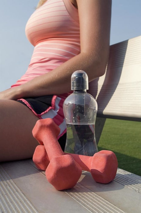 Photographed at a track field, this young woman was taking a break from her workout, sitting on a bench along-side a running track. On the bench beside her was a partially-filled water bottle for the purpose of rehydration, and a pair of light-weight dumbbells, which she used during her warm-up period.