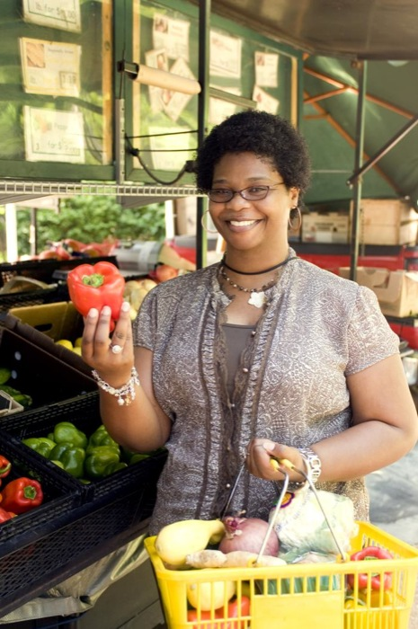 With her shopping basket filled with an array of healthy food choices, this woman had completed her selection process at a mobile produce market, and was shown holding up a bright red bell pepper. Some of the vegetables she'd placed into her basket included a lemon, a head of cauliflower, a purple and a white onion, ginger root, and a variety of bell peppers.