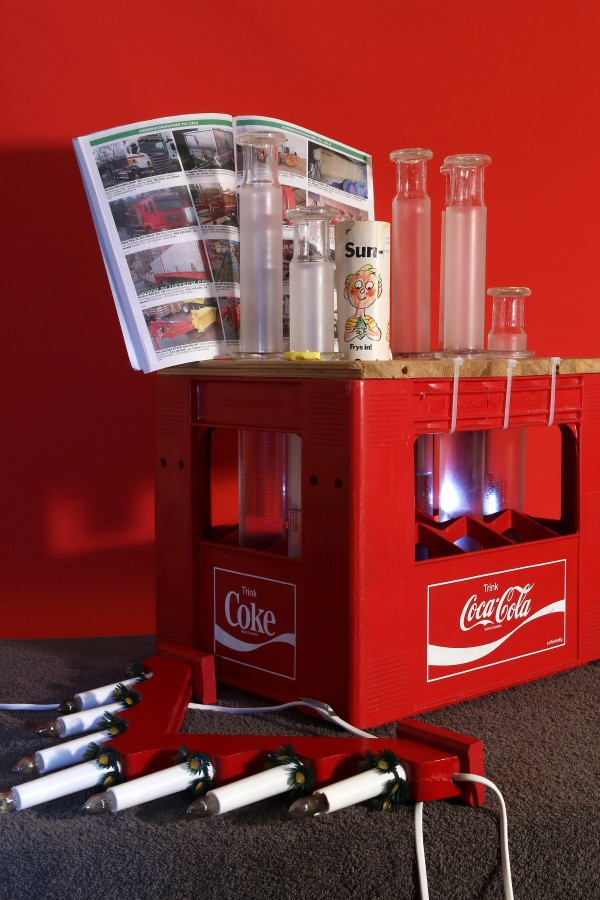 Agricultural machinery classifieds, christmas candlestick, comic magazine and glass syringes in custom made coke crate on towel and tablecloth, Josef Bull, 2014