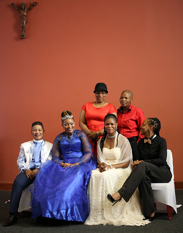 Pastor Zungu (far left) and wife MaGesh (femme in royal blue dress). They have 2 children.