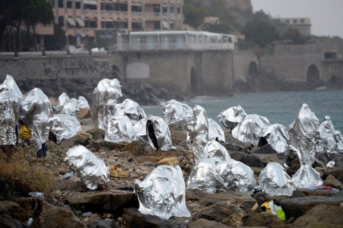 Refugees take shelter on Rocky Italian seafront after being turned away from France.  Published on June 14, 2015 on The Independent. Getty/AFP.