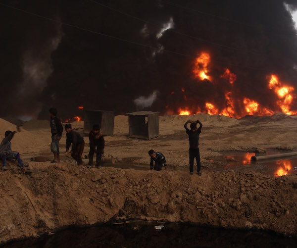 Iraqi children younger than the war tossing rocks into a pool of crude oil.